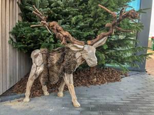 Aus Holz geschnitzter Elch mit Hörnern aus Ästen vor Tannenbaum