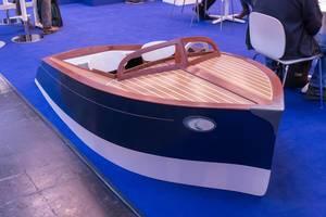 Aus Holz nachgebaute Miniatur eines luxuriösen Schnellboots auf blauem Teppich an Messe