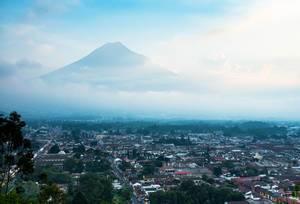 Ausblick über Antigua in Guatemala, im Hintergrund imposanter, von Wolken teilweise verhüllter Vulkan