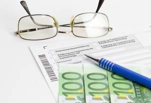 Ausfüllen der Steuererklärung mit einem Kugelschreiber, einer Brille und Euroscheinen