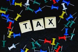 """Ausgebreitete Reißzwecken mit """"Tax"""" (Steuern) - Text auf schwarzem Untergrund"""