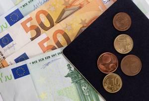 Ausgefächerte fünfzig und einhundert Euro-Geldscheine mit beiliegenden fünf und zehn Cent-Münzen auf samtig schwarzer Unterlage - Nahaufnahme
