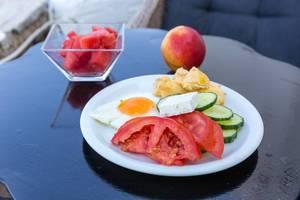 Ausgewogene Mahlzeit mit frischem Gemüse, Spiegelei, Fetakäse, Apfel und geschnittener Wassermelone, auf der griechischen Insel Paros