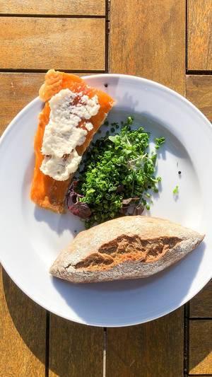 Ausgewogenes Mittagessen mit Fisch - Räucherlachs, Lauchzwiebelsalat und einem Vollkornbrötchen