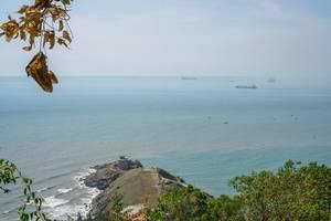 Aussicht von einem Berg in Vung Tau auf das Meer, eine kleine, angrenzende Insel und vorbeiziehende Boote