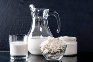 Auswahl frischer Milchprodukte – Kuhmilch, Hüttenkäse und Sauerrahm in Glasbehältern