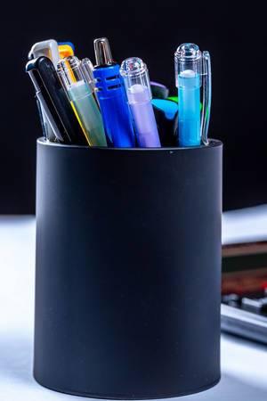 Auswahl von Schreibern in Becher auf Arbeitsplatz