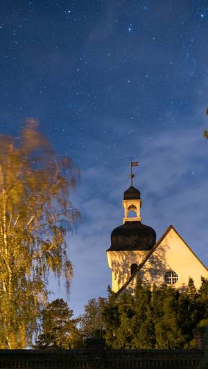 Authentic German protestant church at night with the starry sky above it.jpg