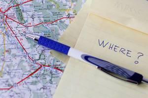 Autokarte, Notizbuch und Kugelschreiber