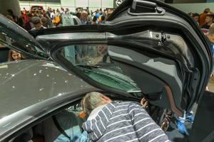 Autoliebhaber und IAA-Messebesucher betrachten die Flügeltüren des  BMW i8 Hybridwagen Ultimate Sophisto Edition