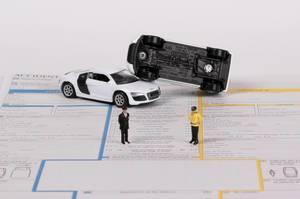 Autounfall mit zwei Spielzeugautos und zwei Polizisten auf einem Schadenbericht für die Versicherung