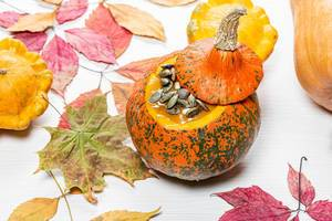 Autumn background with colorful dry leaves and pumpkins on a white wooden background (Flip 2019)