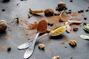 Autumn food composition- spoons with cooking spices, leaves, walnuts