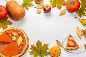 Autumn frame with leaves, pumpkin pie, pumpkins, apples and homemade cookies on white wooden background