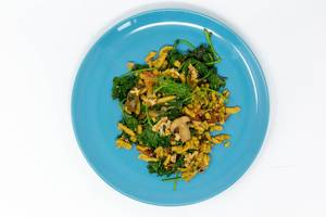 Autumn Spätzle Noodles with kale, mushrooms, tomatoes and roasted walnuts on a blue plate