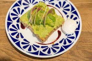 Avo-Toast from whole wheat sliced bread with guacamole, pistachio, yuzu & açai sauce, nutritional yeast and poached egg in Flax&Kale in Barcelona, Catalonia