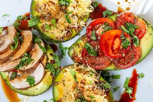 Avocado halves stuffed with mushrooms, cheese, tomatoes and herbs. Top view (Flip 2019)