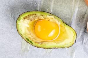 Avocado mit einem rohen Ei in der Mitte, liegt zum Backen bereit auf einem Backpapier