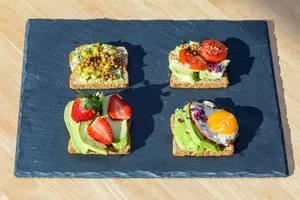 Avocado-Toasts mit Linsen, Erdbeeren, Spiegelei und Tomaten