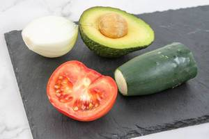 Avocado Tomato Onion and Cucumber on the black tray