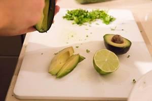 Avocado und Limette auf einem Schneidebrett