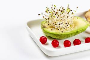 Avocado with micro-green onions and cranberries