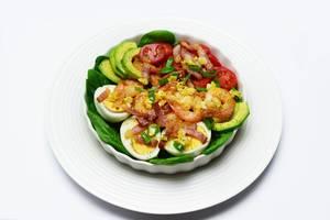 Avocadosalat mit ganzen Garnelen, gebratenem Speck, halbierten Cherrytomaten, Spinat und gekochten Eiern