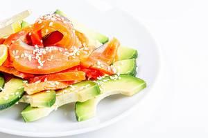 Avocadoscheiben und Räucherlachs verziert mit Sesamkörnern auf einem weißem Teller