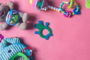 Baby-Spielzeuge wie Babyrassel, Beißring und Plüschtiere auf rosarotem Hintergrund