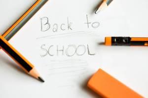 Back to School geschrieben auf Papier zwischen mehreren Bleistiften