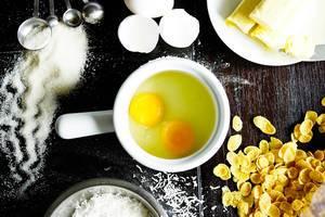 Back-Zutaten für ein Rezept auf einem Tisch - Eier, Kornflakes, Zucker und Butter  - Aufsicht