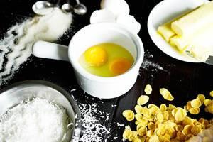 Back-Zutaten für ein Rezept auf einem Tisch - Eier, Kornflakes, Zucker und Butter