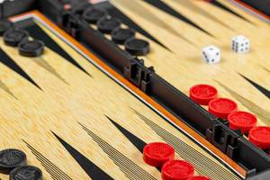 Backgammon board with black and red checkers and dice