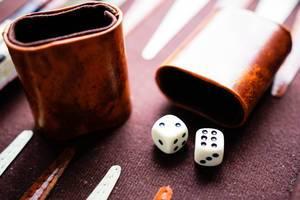Backgammon Würfelbecher mit Würfeln auf einem Backgammonbrett