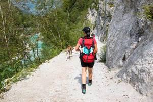 Backpacking: Frau wandert mit Hund an einer Felswand, am Fluß Isonzo / Soča in Slowenien