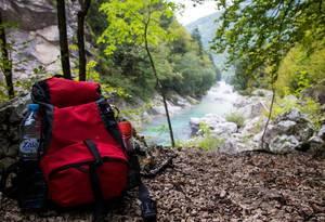 Backpackung-Konzept: Rucksacktour in den Bergen, mit Fluß im Hintergrund