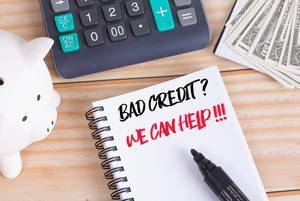Bad credit? We can help! text in notebook with piggy bank and calculator on wooden table