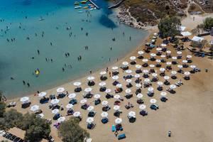 Badegäste im Mittelmeer und auf Strandliegen, unter weißen Sonnenschirmen, am weißen Sandstrand Monastiri auf Paros