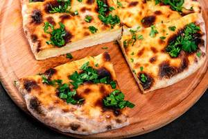 Baked khachapuri with cheese on a round kitchen Board