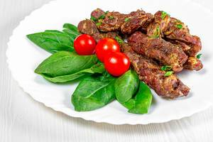 Baked lamb with spinach and cherry tomatoes