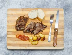 Baked meat on wooden board