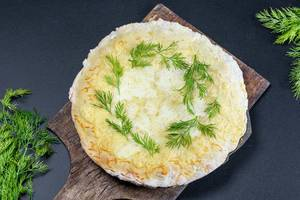 Baked meat pie with cheese and herbs