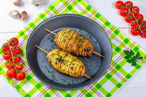 Baked potatoes on skewers with herbs and cherry tomatoes. Top view