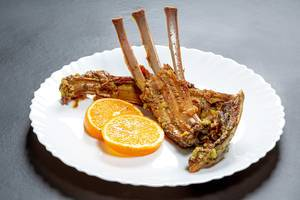 Baked ribs of young lamb with slices of fresh orange in a plate on a black background