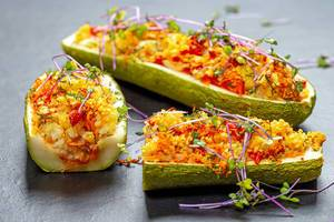 Baked zucchini with vegetables and couscous on a black background with micro green cabbage (Flip 2019)