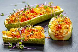 Baked zucchini with vegetables and couscous on a black background with micro green cabbage