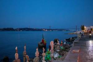 Balanced stone towers and 25 de Abril bridge