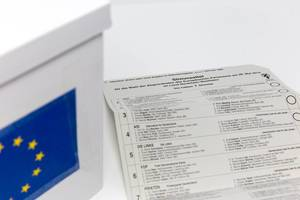 Ballot paper of the postal voting documents for the European election 2019, with a list of participating German parties, next to an EU ballot box