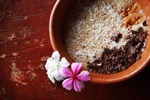 Banana smoothie bowl topped with coconut flakes, sesame seeds, raw chocolate and peanut butter