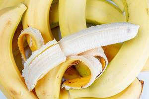 Bananas background with peel and peeled